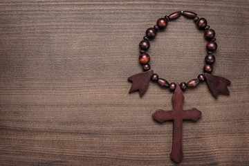 wooden cross on brown table background