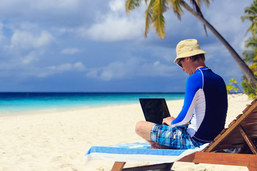 man with laptop on beach vacation