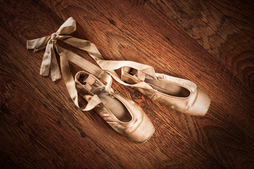 Pair of ballet shoes on a wooden floor