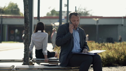 Angry businessman talking on cellphone with documents on bench
