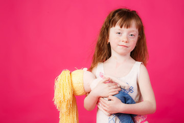 beautiful girl with red hair hugging her doll and smiling