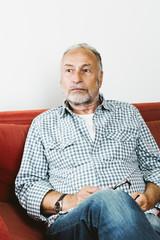 Rentner (m/71) sitzt auf Sofa, nachdenklich, Studio