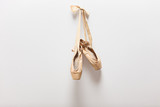Pair of old ballet shoes hanging on a wall