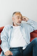 Rentner sitzt entspannt auf Sofa