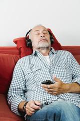 Rentner entspannt auf Sofa, smartphone und Kopfhörer