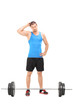 Doubtful male athlete looking at a barbell