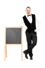 Male waiter standing next to a blackboard