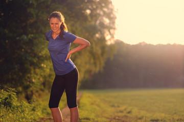 Frau hat Rückenschmerzen beim Sport