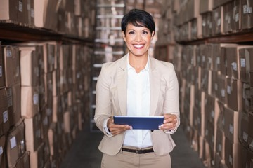 Pretty warehouse manager holding tablet pc