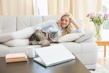 Happy blonde with pet cat on sofa