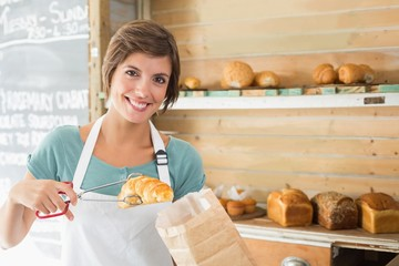 Pretty waitress picking up croissant