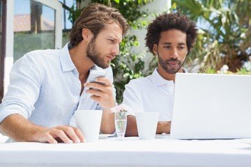 Two friends having coffee together with laptop