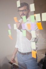 Casual businessman looking at sticky notes