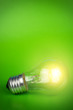 glowing light bulb over green background