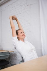 Businesswoman stretching hands in office