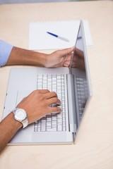 Hands using laptop at desk