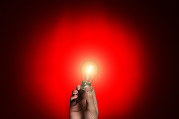 light bulb in hand on red background