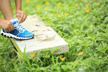 young woman hiking tying shoelace on stone bench in forest grass