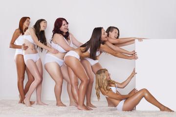Natural girls in underwear pulling whiteboard