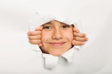 Cute little girl peeking through paper