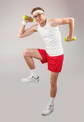 Geeky hipster posing in sportswear with dumbbells