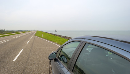 Car parked on a road along a dike along a lake