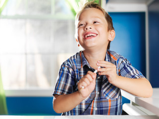 little boy with pencil laughing