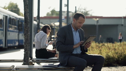 Young businessman with tablet sitting on bench in the city