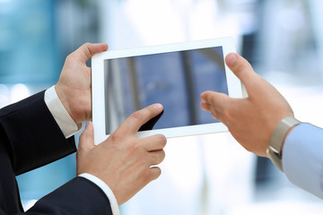 Image of two young businessmen using touchpad