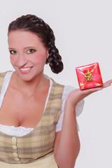 Junge bayerische Frau im Dirndl mit einem kleinen Geschenk