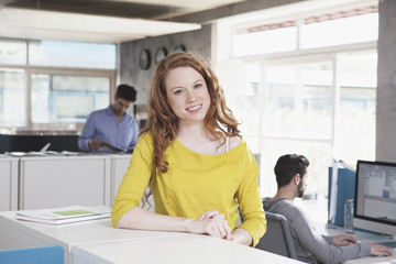 Lächelnde Frau, stehend in einem offenen Großraumbüro