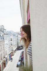 Frankreich, Paris, Lächelnde junge Frau Frau schaut aus dem Hotelfenster