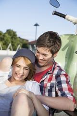 Glückliches Teenager-Paar auf Motorroller