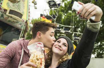 Teenager-Paar mit Popcorn macht Selfie auf Kirmes