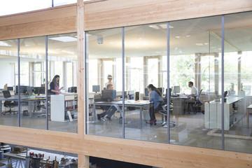 Team von fünf Geschäftsleuten an Arbeitsplätzen in modernem Büro