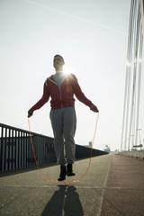 Junger Mann auf der Brücke, Springseil