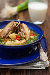 shurpa - Asian mutton soup in blue plate on a dark wooden table