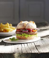 Hamburger auf Teller und Pommes frites dazu
