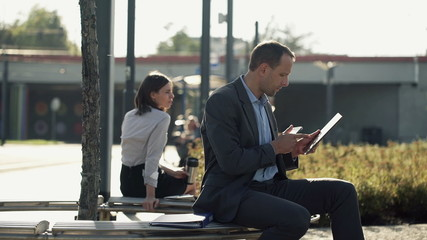 Businessman comparing data on smartphone and tablet in the city
