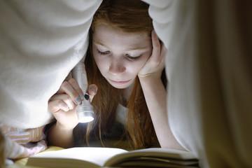 Mädchen liest ein Buch heimlich im Bett unter der Decke