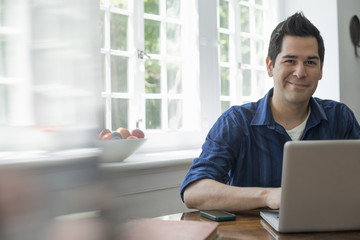 A man using a laptop seated at a table by a window.