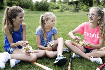 Drei Mädchen sitzen auf einer Wiese und chillen