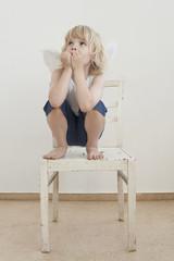 Portrait des kleinen Jungen mit Flügeln, hockend auf einem Stuhl