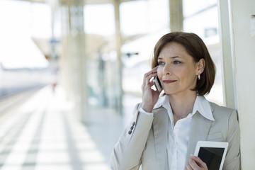 Geschäftsfrau telefoniert auf Bahnsteig