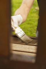 Mann lasiert Holzbank
