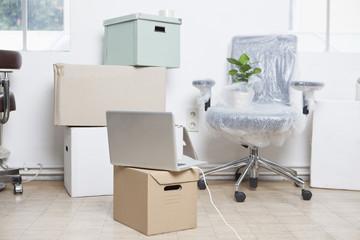 Stapel von Kartons, eingewickelter Drehstuhl und ein Notebook in einem Büro