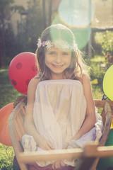 Lächelndes Mädchen mit Blumen, sitzend auf einem Handwagen im Garten