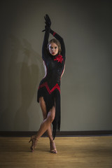 Dancer in dance studio. A woman in a black dress.
