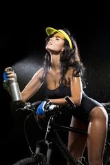 Frau mit Mountainbike erfrischt sich mit Wasser