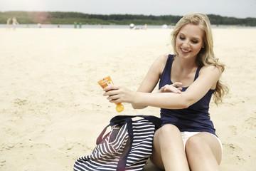 Lächelnde junge Frau sitzt am Strand mit Sonnencreme